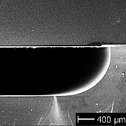 SEM picture of a cross-sectional view (fracture edge) of a glass substrate bonded to a structured glass substrate.